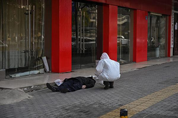2020年1月30日,一名穿著防護服的官員正在檢查一名戴著口罩的倒斃在武漢街道上的老人。(Hector RETAMAL/AFP)