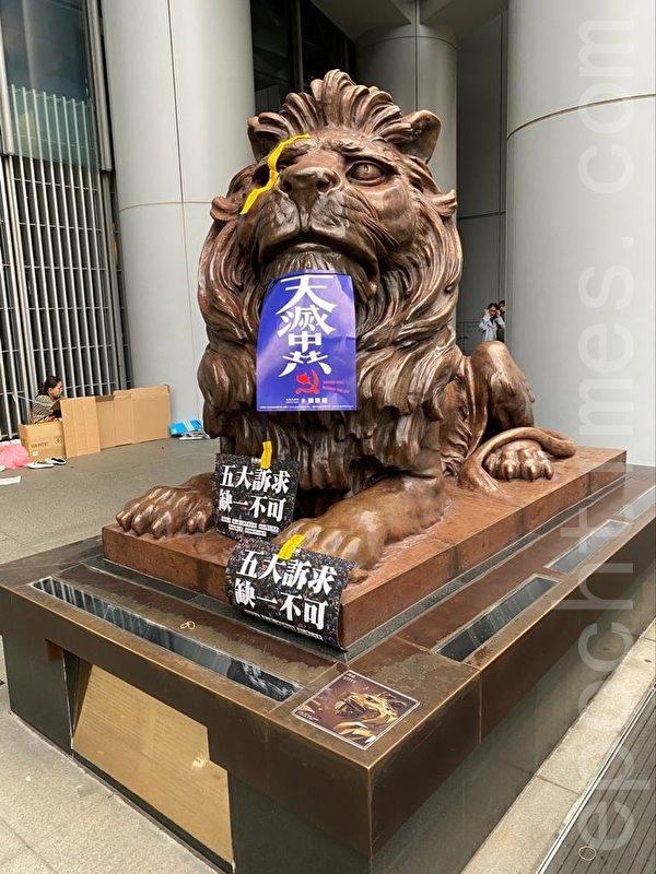2020年1月1日,香港元旦由民陣舉辦「元旦大遊行」,以「毋忘承諾 並肩同行」為主題。中環遊行者創意將「天滅中共」、「五大訴求,缺一不可」標語海報黏貼於獅身上。(謝恩慈/大紀元)
