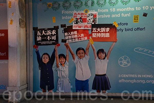 2020年1月1日,香港元旦由民陣舉辦「元旦大遊行」。圖為遊行者創意將標語海報黏貼於法國文化協會廣告上。(文瀚林/大紀元)