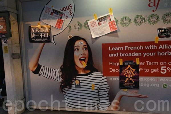 2020年1月1日,香港元旦由民陣舉辦「元旦大遊行」。圖為中環匯豐銀行廣告被貼上「天滅中共」及黃色避邪符咒。(文瀚林/大紀元)