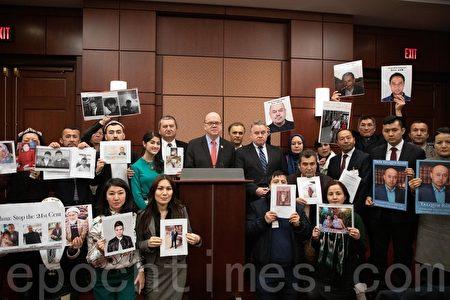 麥克高文(Jim McGovern)和史密斯(Chris Smith)議員與部份與會者合照,他們的家人和朋友在中國遭受迫害。(林樂予/大紀元)