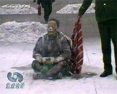 電視上的王進東,渾身燒得焦黑,兩腿間盛汽油的塑料雪碧瓶卻完好無損。(影片截圖)