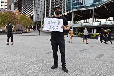 1月19日,參加「全球連線 制裁中共」集會的一位布市居民手舉「反共抗暴撐港人」的展板,呼籲澳洲政府制裁中共。(楊裔飛/大紀元)