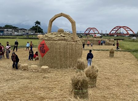 七座稻草装置艺术及游艺设施放置田地中。