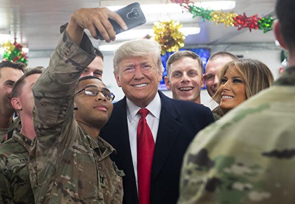 2018年12月26日,特朗普與阿薩德空軍基地的士兵合照。(SAUL LOEB/AFP via Getty Images)