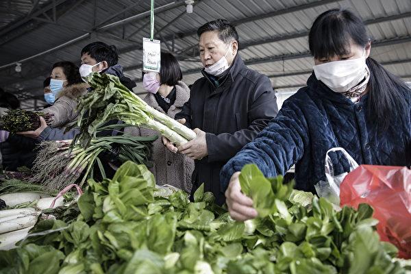 武漢市民戴口罩排隊到超市買菜。(Photo by Getty Images)
