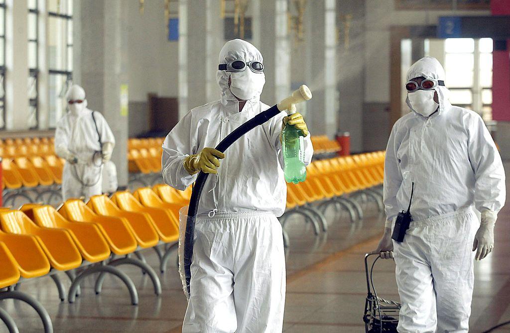 武漢爆發不明肺炎疫情,疑薩斯再現。圖為2003年北京薩斯期間,工作人員在火車站候車室消毒。(PETER PARKS/AFP/GettyImages)