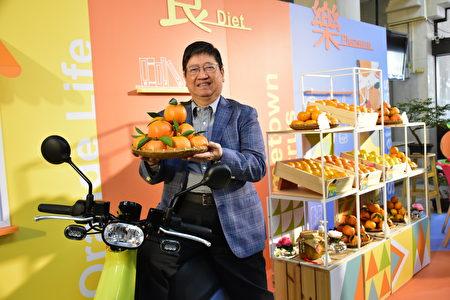 杨县长捧着黄澄澄的柑桔与gogoro电动车合影。