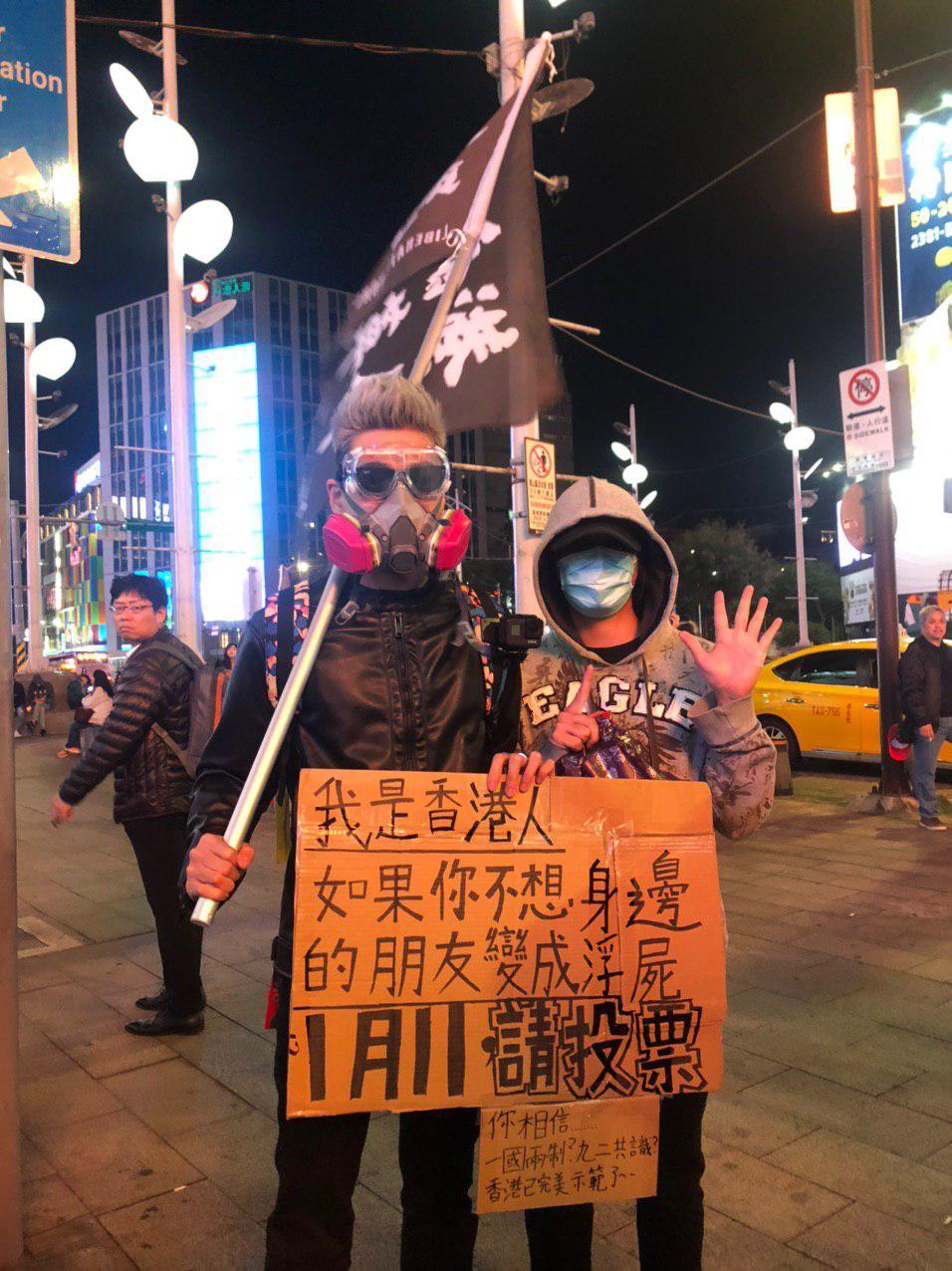 香港人在台灣西門町舉牌呼籲台灣人珍惜手中選票。(梁珍 / 大紀元)