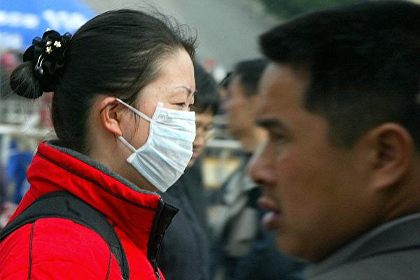武漢爆發疑似SARS的不明病毒性肺炎,民眾如何防範?圖為2004年戴口罩預防SARS的中國民眾。(LIU JIN/AFP/Getty Images)