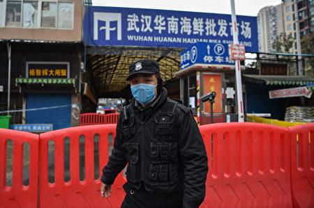 1月25日一名公安站在華南市場外。(Hector RETAMAL/AFP)