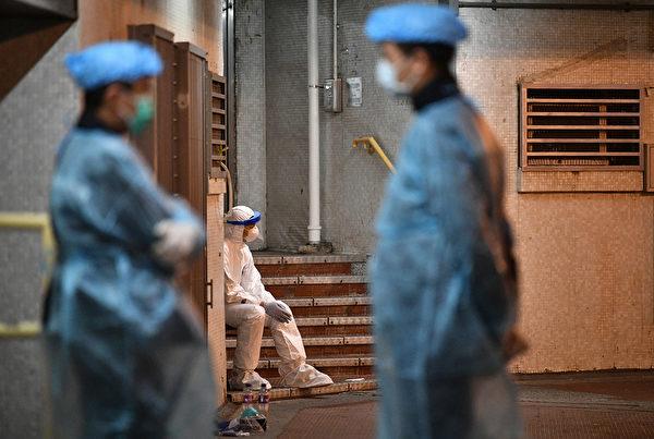 2020年2月11日凌晨,身穿防護服的醫務人員住在香港一個居民區的街區入口附近,該街區有兩個人感染了中共病毒。(Photo by Anthony WALLACE/AFP)