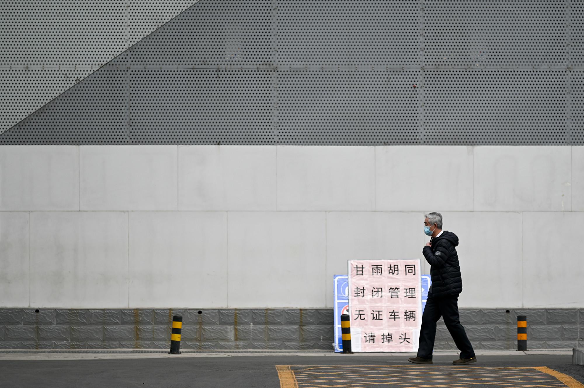 北京的中共病毒肺炎疫情形勢嚴峻,很多地區都實施封閉式管理。圖為2020年2月25日,一名戴著口罩的老人在北京的一條空蕩蕩的道路上行走。(STR/AFP)