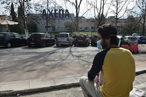 2020年2月26日,一名帶孩子的男子在塞薩洛尼基Ahepa醫院外戴著口罩。希臘於2020年2月26日報告了第一宗中共病毒病例,是一名最近去過意大利北部的婦女。(Sakis MITROLIDIS/AFP)