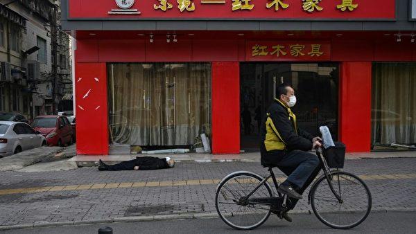 1月31日一位白髮老人倒臥武漢街頭,這一幕恰好被法新社記者親眼目睹。(AFP)