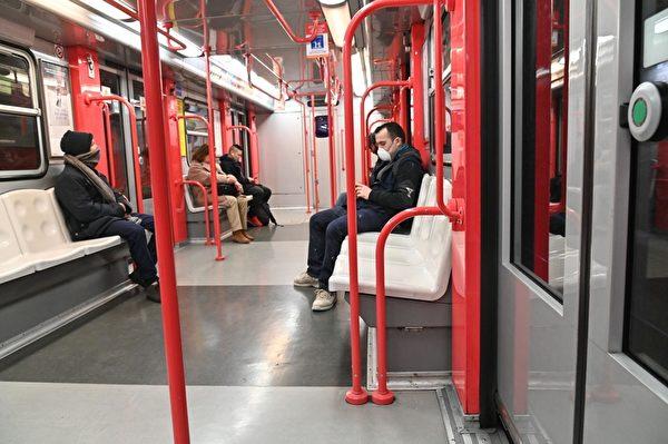 2020年2月24日,意大利北部新冠肺炎擴散,超過十座城鎮「封城」兩周。圖為米蘭市中心,一名戴著防護口罩的男子坐在地鐵裏看著的手機。(ANDREAS SOLARO/AFP via Getty Images)