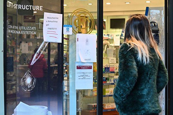 2020年2月24日,意大利北部新冠肺炎擴散,超過十座城鎮「封城」兩周。圖為在米蘭市中心大教堂廣場旁的藥房窗戶上,一名婦女看著寫著「Amuchina凝膠和呼吸面罩售罄」的告示。 (ANDREAS SOLARO/AFP via Getty Images)