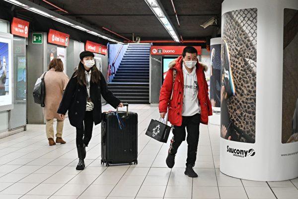 2020年2月24日,意大利北部新冠肺炎擴散,超過十座城鎮「封城」兩周。圖為在米蘭市中心的Duomo地鐵站,戴著防護口罩的遊客拖著行李。(ANDREAS SOLARO/AFP via Getty Images)