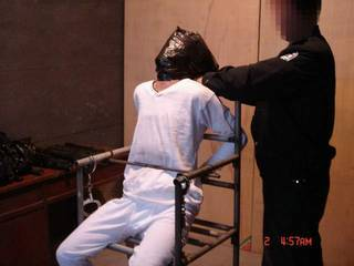 酷刑演示:膠袋套頭。(明慧網)