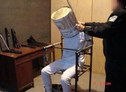 中共黑獄酷刑演示:鐵桶敲頭。(明慧網)
