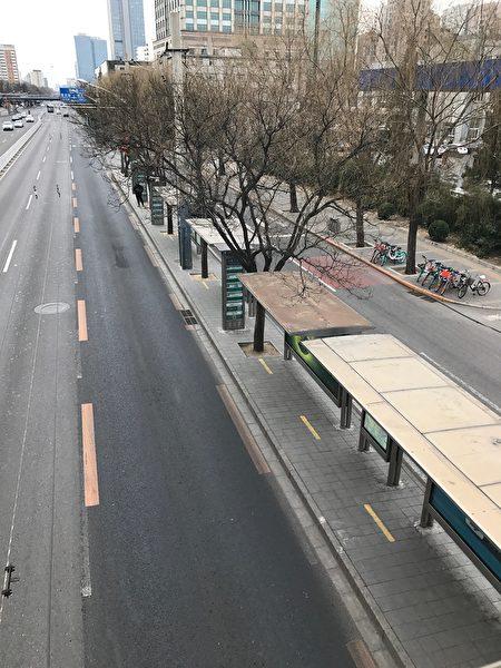 2月27日中午11點街景,從北京炎黃藝術館過街天橋上往下看,路上空空盪盪,公交站是:炎黃藝術館公交站。(大紀元)