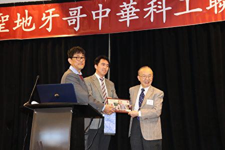 圣地亚哥中华科工会会长曹力峰(左)与副会长叶绍阳(中)为钱煦院士(右)送上纪念相册。(邓舒语/大纪元)