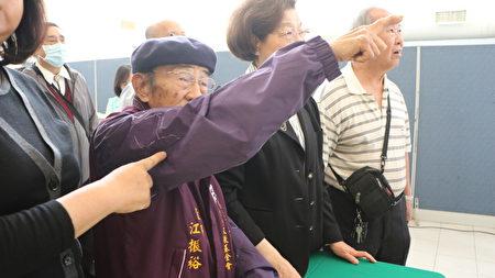 现任二二八纪念文教基金会董事江振裕手指着墙上二哥江振猷遗照,说二哥很孝顺。监察院长张博雅(右2)在一旁。