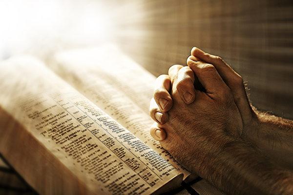 一名男子在《聖經》前禱告。(Fotolia)