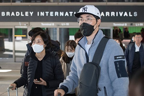 美國總統特朗普周五(1月31日)簽署命令,拒絕在抵達美國前14天曾到過中國的外國人士入境,但排除適用綠卡持有者(合法永久居民)及部份外國人士。圖為1月29日帶著面罩的旅客抵達洛杉磯國際機場。(MARK RALSTON/AFP via Getty Images)