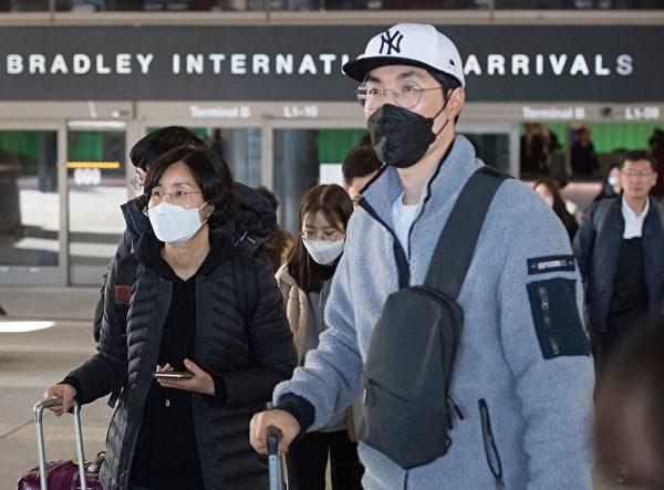 圖為1月29日戴著口罩的旅客抵達洛杉磯國際機場。(MARK RALSTON/AFP via Getty Images)