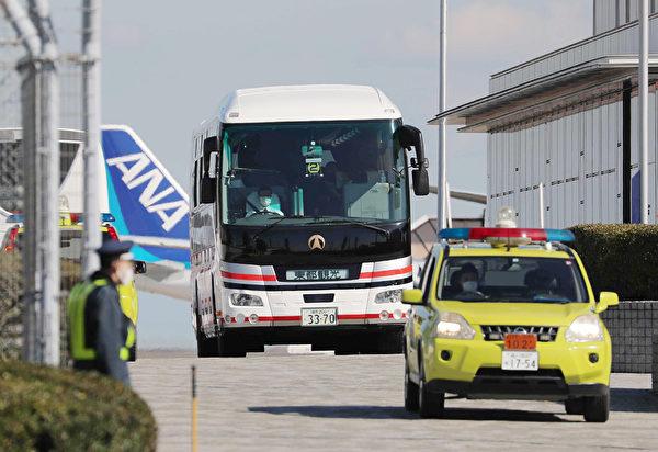 2020年1月30日,搭第二架包機從武漢撤離的日本僑民下了飛機後,登上一輛巴士,由警車開路前去隔離。(STR/JIJI PRESS/AFP)