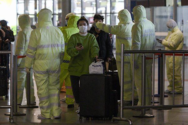 2月9日上海南火車站,穿上防護衣的醫護人員查閱乘客的旅遊行程。(NOEL CELIS / AFP)
