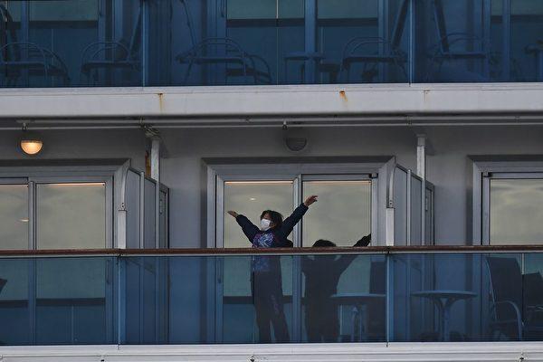 真正的隔離應該是房間、通風系統、與飲食和飲水相關的衛生系統都要隔離,但郵輪沒有這樣的條件。圖為鑽石公主號的乘客站在陽台上。(CHARLY TRIBALLEAU/AFP via Getty Images)