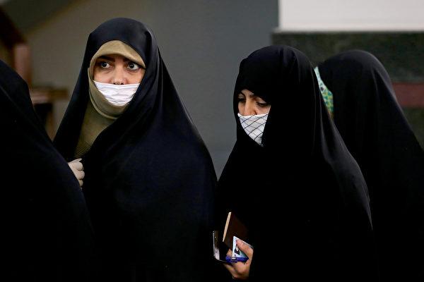 中共肺炎疫情在伊朗急速升溫。圖為2020年2月21日戴著防護口罩投票的伊朗民眾。(ATTA KENARE/AFP)