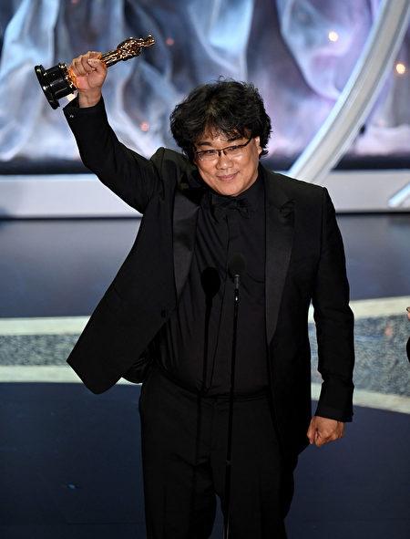 南韓電影《上流寄生族》(台譯:寄生上流,Parasite)的奉俊昊(Bong Joon Ho)興奮地舉起小金人。(Kevin Winter/Getty Images)