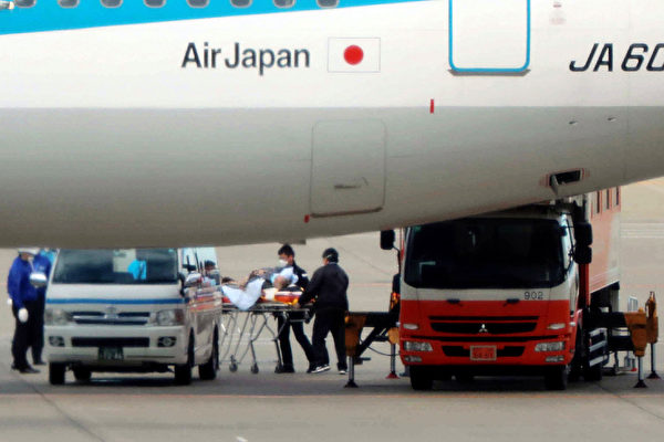 2020年1月31日,日本政府安排的從中國武漢出發的第三次包機航班抵達東京羽田機場後,被撤離的一名乘客被擔架運送。(Photo by STR / JIJI PRESS / AFP)