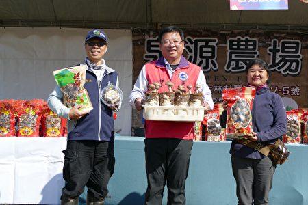 魚池鄉長劉啟帆(中)與香菇業者在燈會現場的香菇展售攤位前合影。