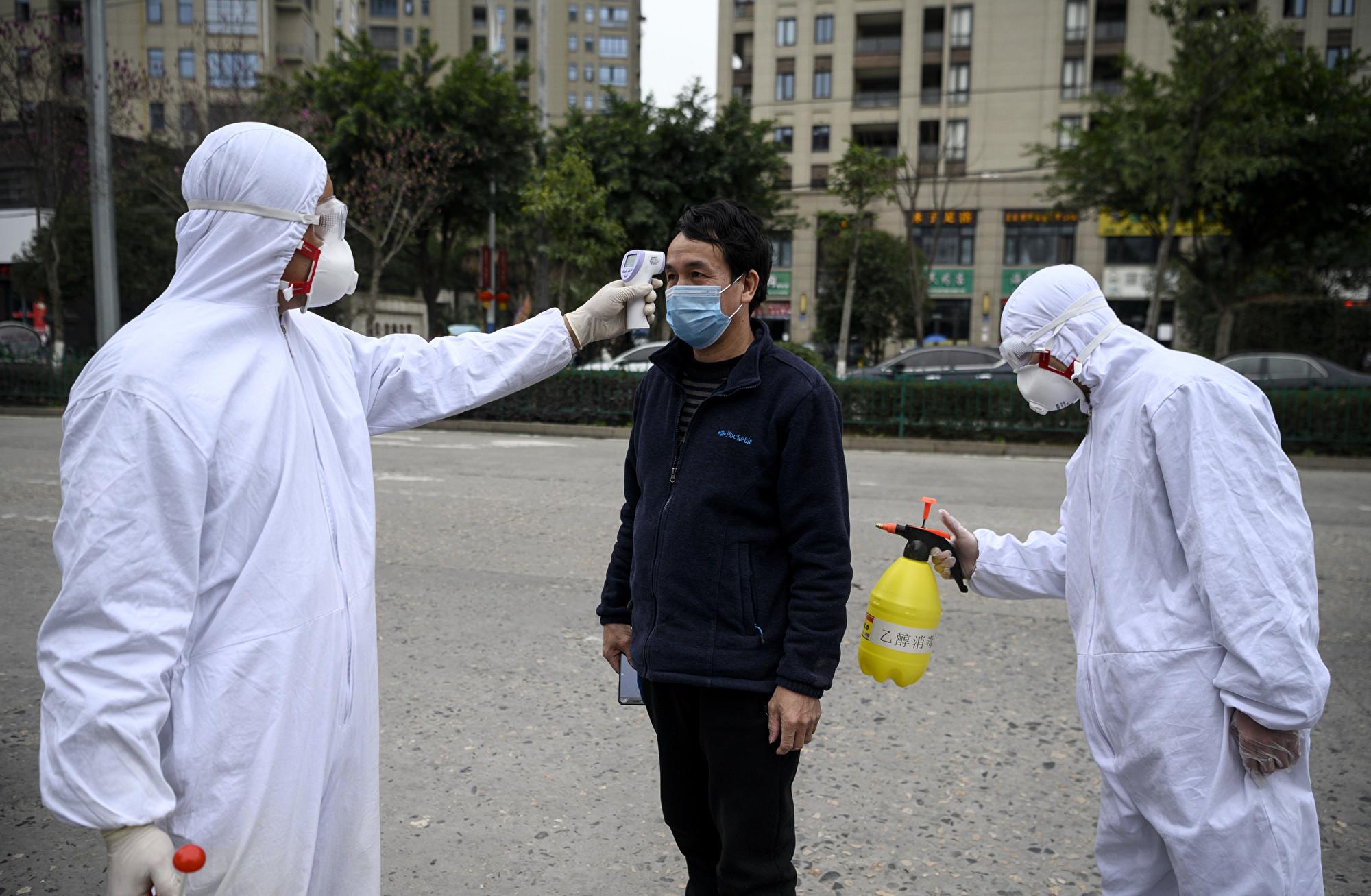 中共近期要求企業復工,以避免中共肺炎持續影響中國經濟,並期待V型復甦。然而,經濟學家認為,疫情蔓延全球,中國經濟難有起色。圖為溫州一家工廠安保人員正在檢測一名員工的額溫。(NOEL CELIS/AFP)