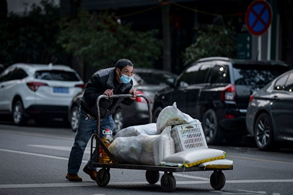 2020年3月3日,湖北省武漢市,推著推車的男子戴上口罩防護。(STR/AFP via Getty Images)