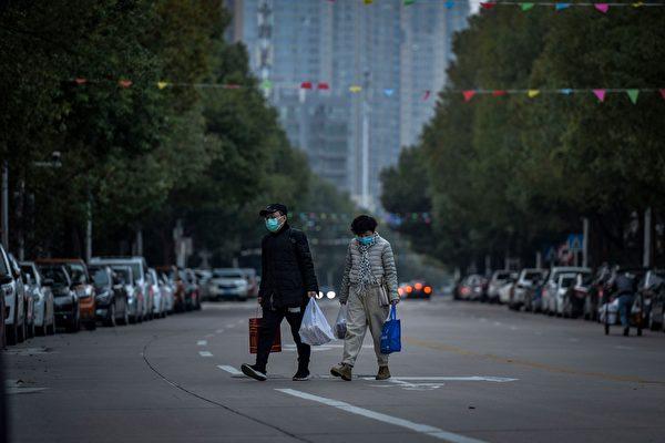2020年3月1日,湖北省武漢市,居民戴著口罩穿越空蕩蕩的街道。(STR/AFP via Getty Images)