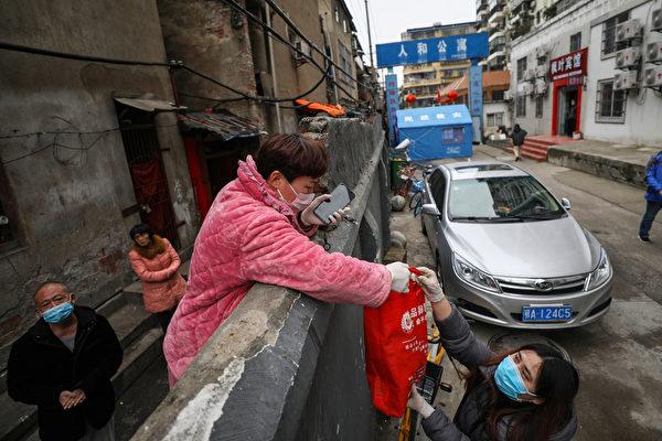 2020年3月3日,湖北省武漢市,一小區內的居民(中)透過圍牆接收食物。(STR/AFP via Getty Images)