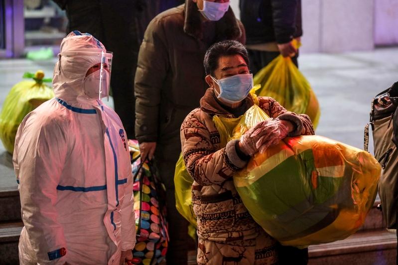 圖為2020年3月3日,武漢感染中共病毒(武漢病毒、新冠病毒)的患者(中)等待從武漢市第五醫院轉移到新建的雷神山醫院。(STR/AFP via Getty Images)