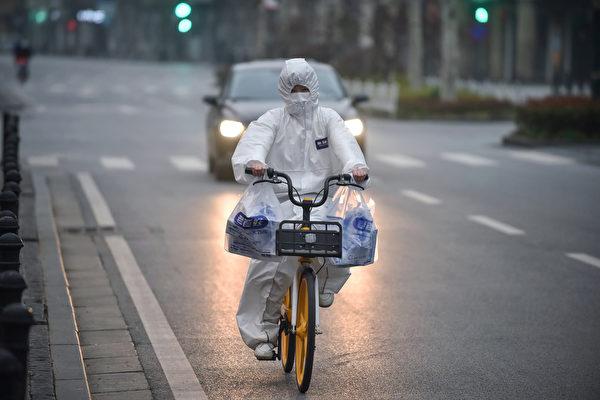 2020年2月27日,湖北省武漢市,一騎車民眾穿戴防護衣。(STR/AFP via Getty Images)