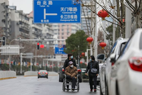2020年3月4日,湖北武漢,街道來往人車稀少,外出民眾紛紛戴上口罩。(STR/AFP via Getty Images)