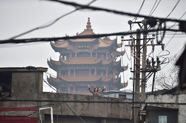 2020年2月26日,湖北省武漢市,小區進出受管制,一民眾向外界打招呼。 (STR/AFP via Getty Images)