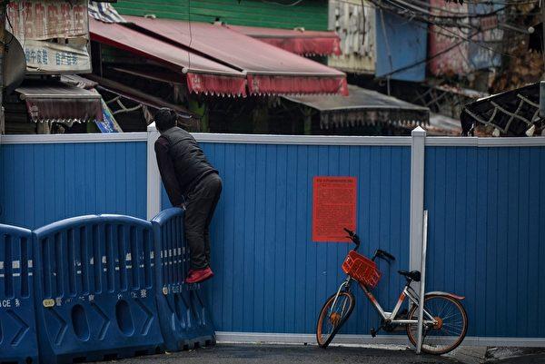 2020年3月4日,湖北省武漢市,小區進出受管制,民眾爬上路圍欄向內張望。(STR/AFP via Getty Images)