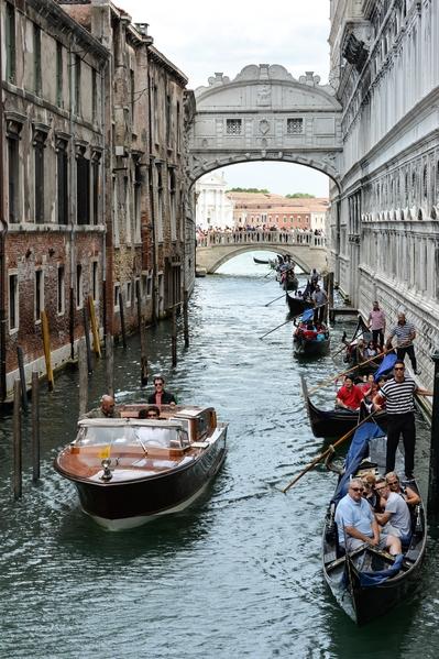 2015年6月20日,威尼斯的運河上,遊客乘坐小船通過嘆息橋。(ANDREAS SOLARO/AFP via Getty Images)