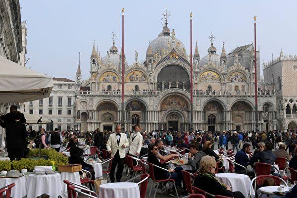 2017年10月20日,大批遊客在威尼斯聖馬可大教堂前的一家餐廳休息。(MIGUEL MEDINA/AFP via Getty Images)