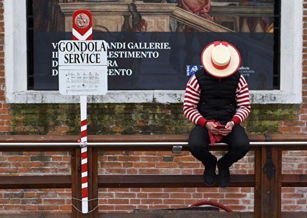 2020年3月5日,意大利威尼斯,在中共肺炎疫情下現正處於封城狀態。圖為貢多拉船夫等待遊客上門時無聊滑手機。(ANDREA PATTARO/AFP via Getty Images)