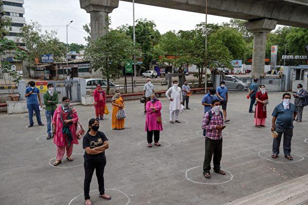 為了因應中共病毒疫情延燒,印度總理莫迪宣佈,從25日零時開始,全境封鎖21天。圖為2020年3月26日,阿默達巴德的民眾在一間商店外等待購物時,站在畫好的圈圈內保持距離。(SAM PANTHAKY/AFP via Getty Images)